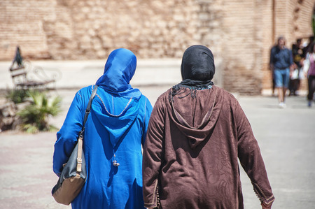 arab hijab: Two moroccan women seen from the back dressed in typical blue and brown djellaba walk down the streets of Marrakesh Medina, Morocco