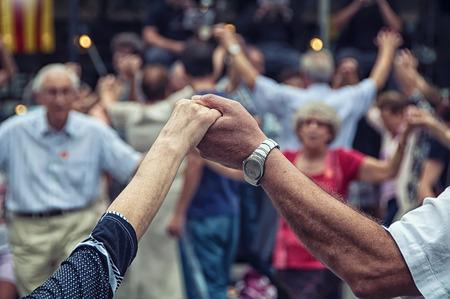 Pohled seniorů se drží za ruce a tančí národní taneční Sardana Plaza Nova, Barcelona, Španělsko. Jedná se o typ kruhu tance typické Katalánska