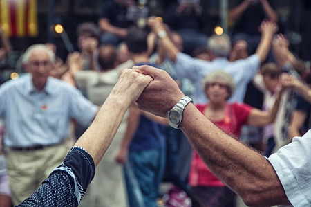 View of senior people holding hands and dancing national dance Sardana at Plaza Nova, Barcelona, Spain. It is a type of circle dance typical of Catalonia Imagens