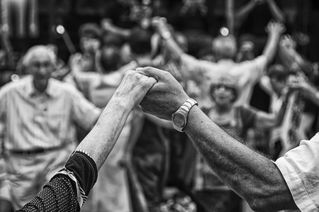 View of senior people holding hands and dancing national dance Sardana at Plaza Nova, Barcelona, Spain. It is a type of circle dance typical of Catalonia Stock Photo