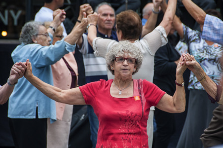 BARCELONA, SPAIN - SEPTEMBER 15, 2013: Close view of people seniors dancing Sardana at Plaza Nova. The dance is a type of circle dance typical of Catalonia.
