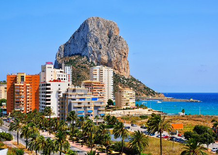 Mediterranean summer Resort Calpe, Costa Blanca, Spain with mountain Penon de Ifach and sea. Various buildings at the seashore - hotels, apartments, skyscrapers. Palm trees.