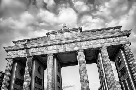 historical events: Brandenburg Gate - a Triumphal Arch, one of the most popular landmarks in Berlin. It is a site for major historical events and a historical symbol of the capital of Germany. Black and white Stock Photo