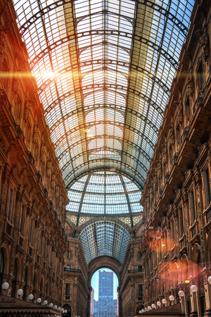 MILAN, ITALY - JULY 7, 2013: Interiors of Galleria Vittorio Emanuele II - world famous shopping mall toped with a glass dome. Popular city landmark. Lens flare, sunlight