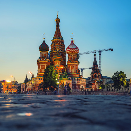 red pebble: Saint Basil Cathedral in Moscow, Russia on Red Square at sunset. Blurred people and pebble pavement at the foreground Stock Photo