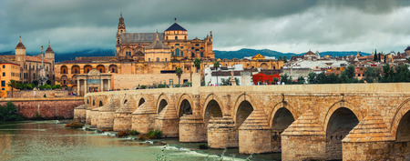 CORDOBA, SPAIN - OCTOBER 10, 2014: Roman bridge across the Guadalquivir river and La Mesquita Cathedral with people walking around sightseeing. Popular touristic place, toning effect