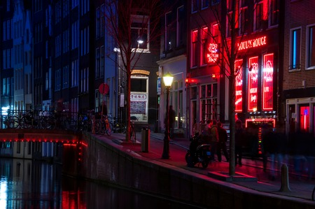 adult sex: AMSTERDAM, NETHERLANDS - MARCH 16, 2014: Night view of Red - light district, where is a concentration of sex shops, strip clubs, adult theaters, etc. Facade of Moulin Rouge Theater Editorial