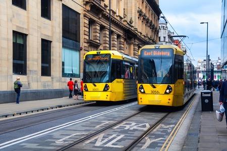boroughs: MANCHESTER, UK - SEPTEMBER 3, 2014: Light rail Metrolink tram in the city center. The system has 77 stops along 78.1 km and runs through seven of the ten boroughs