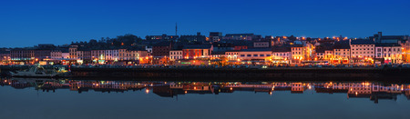 WATERFORD, IRELAND - NOVEMBER 29, 2014: Panoramic view of a cityscape at night with illumination. It is the oldest city in the country where located many restaurants, shops, bars. Moored ship.