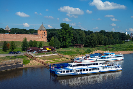 volkhov: VELIKIY NOVGOROD, RUSSIA - AUGUST 10, 2015: Kremlin wall and tower in summer with green trees and cloudy blue sky. Popular landmark, touristic boats moored at the pier. Volkhov river Editorial