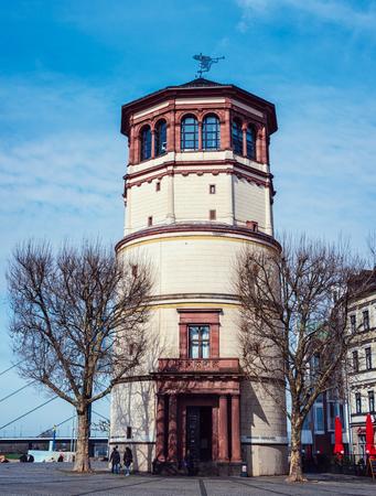 altstadt: DUSSELDORF, GERMANY - MARCH 19, 2014: People in front of Schlossturm in Altstadt in the sunny spring day. Famous landmark in the city