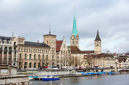 church tower: St. Peter Church and old Clock tower is one of the symbols of the city and major touristic attraction in Zurich, Switzerland. Limmat river with moored boats