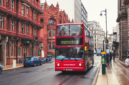 BIRMINGHAM, UK - SEPTEMBER 1, 2014: Red double-decker bus at the street. Old building of the historical part of the city. People, cars and famous restaurants and pubs