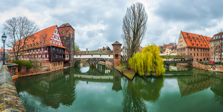 wine store: Wine Store, Max Bridge, Hangmans Bridge over Pegnitz River in Nuremberg, Germany. Reflection in the water and cloudy sky