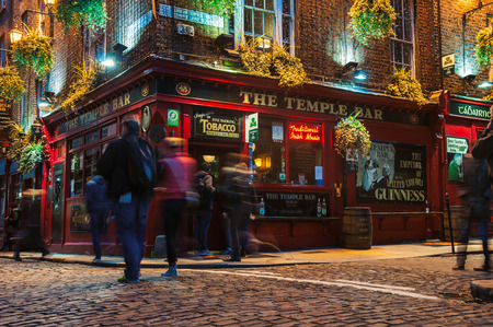 temples: DUBLIN, IRELAND - NOVEMBER 11, 2014: Nightlife at popular historical part of the city - Temple Bar quarter. The area is the location of many bars, pubs and restaurants. People walking inside a pub