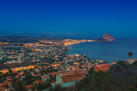 Sunset over the coastline of Mediterranean Resort Calpe, Costa Blanca, Spain with Sea and famous mountain Penon de Ifach. Different buildings - hotels, apartments.