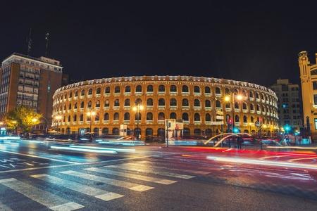 plaza de toros: Night view of a Bullring Arena in Valencia, Spain. Car traffic lighting trail, motion blurred people. Dark sky.