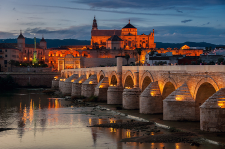 spain: Illuminated Roman bridge and La Mezquita at sunset in Cordoba, Andalusia, Spain. Guadalquivir river