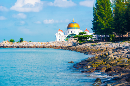 straits: Malacca Straits Mosque, Malaysia located in a man-made island. It is a relatively new and very colorful mosque opened in 2006. Stock Photo