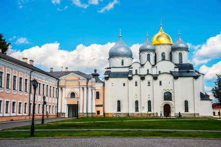 forefront: Cathedral of Holy Wisdom inside a Velikiy Novgorod Kremlin, Russia in summer. Cloudy sky and green grass at the forefront Stock Photo
