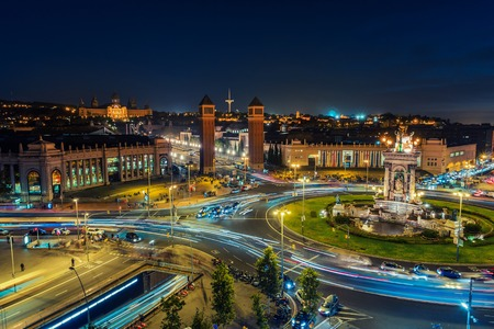 Spanish Square aerial view in Barcelona, Spain at night. This is the famous place with traffic light trails, fountain and Venetian towers, and National museum at the background. Blue sky Фото со стока