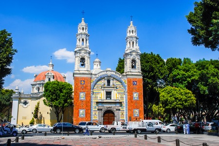 talavera: PUEBLA, MEXICO - MARCH 17, 2011: Our Lady Of Guadalupe Church with cars. It uses the famous local ceramic tiles talavera in colorful patterns on the facade. Famous landmark