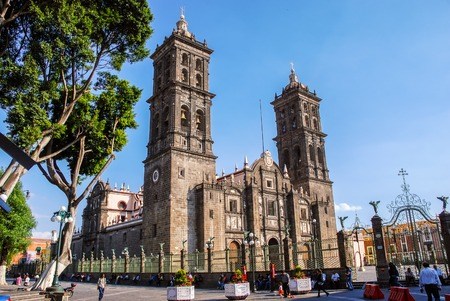 PUEBLA, MEXICO - MARCH 17, 2011: Roman Catholic colonial Cathedral during the day -  consecrated in 1649. It is a major landmark in the city. Clear blue sky, unidentified people
