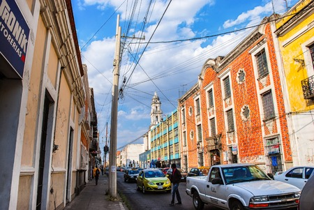 PUEBLA, MEXICO - MARCH 17, 2011: Crowded streets of colonial city during the day. Cars, unidentified people and colorful old houses Editöryel