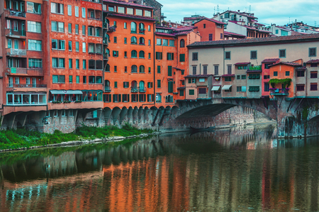 hued: Famous Ponte Vecchio over river Arno in Florence, Italy. It is one of the best bridges in the world. Old historical buildings. Hued colors, toning