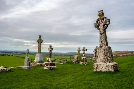 ancient ireland celtic cross: Old cemetery of Rock of Cashel in Ireland with fields at the background. Cloudy sky Stock Photo