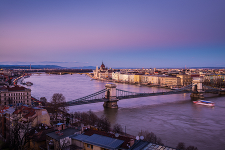 building a chain: Chain bridge and Parliament building in Budapest, Hungary at sunset Stock Photo