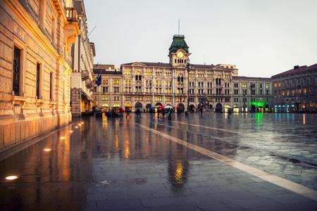 raining: Unidad de Italia Square en Trieste, Italia en la noche durante la lluvia pesada. edificios famosos - ayuntamiento y el cielo nublado. Las personas con paraguas