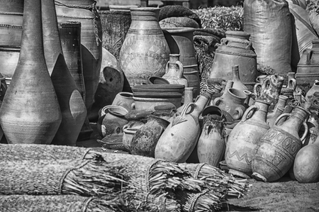 differently: Differently sized dusty Clay pots stuck together at the village market in Moroccan town Ouarzazate. Black and white