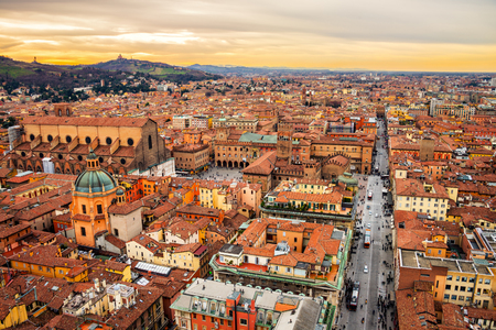 Aerial view of Bologna, Italy at sunset. Colorful sky over the historical city center with car traffic and old buildings