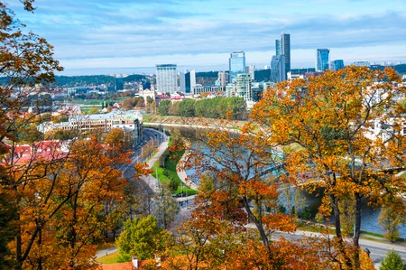 forefront: Aerial view of Vilnius, Lithuania with Autumn Trees in the forefront. Old town was declared a UNESCO World Heritage Site. It is rapidly becoming a modern city with many skyscrapers