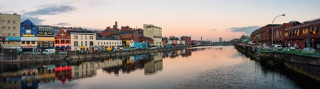 Panoramic view of River Lee quays in Cork, Ireland in the city center with many restaurants, shops, bars and car traffic.