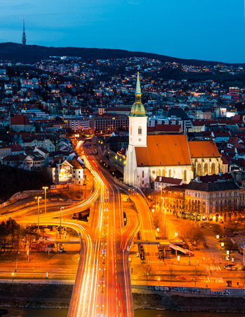 Aerial view of Bratislava, Slovakia at night. Illuminated historical buildings with car traffic at the highway