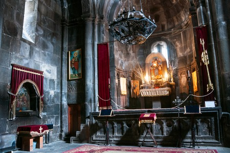 geghard: GOGHT, ARMENIA - MARCH 23, 2016: Inside a Geghard medieval monastery of Kotayk province. Altar ad religious decoration with dim light