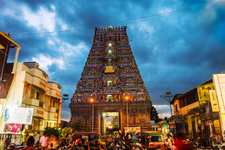 Famous Arulmigu Kapaleeswarar Temple in Chennai, Tamil Nadu, India at night. Illuminated entrance with nightlife around