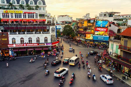 HANOI, VIETNAM - AUGUST 2, 2016: Car and people traffic in the city center. Typical cafes and restaurants. Sunset yellow sky