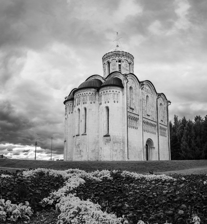 Cathedral of Saint Demetrius in Vladimir, Russia with cloudy weather. White - stone carvings on the exterior walls, flowers at the forefront. Black and white Stock Photo