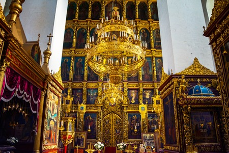 PSKOV, RUSSIA - AUGUST 20, 2016: Inside a Trinity Cathedral. Beautiful religious decoration with golden chandelier and altar, various icons and white columns