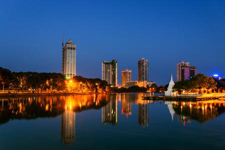 Srí Lanka. Pohled na jezero Beira v Colombu, Srí Lanka s buddhistickým chrámem a osvětlené moderní budovy v noci. Tmavě modrá obloha Reklamní fotografie