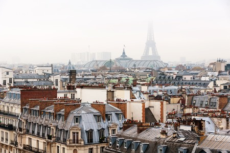 sacred trinity: Paris, France. Aerial view of historical buildings with Eiffel Tower covered with fog in Paris, France with cloudy sky