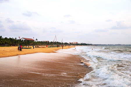 Beach at Negombo, Sri Lanka with evening cloudy sky. Boats and few unidentified people