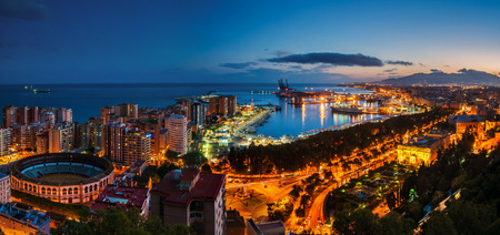 Malaga, Spain. Aerial view of City Hall, port and Bullring arena with illuminated buildings and Mediterranean sea in Malaga, Andalusia, Spain at night with sunset sky