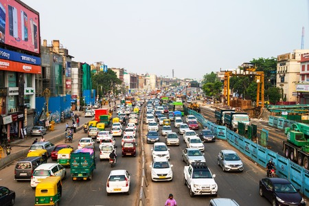 DELHI, INDIA - JULY 5, 2016: Heavy car traffic in the city center of Delhi, India. Buses and construction nearby the road. Various shops, cafes, restaurants Editöryel