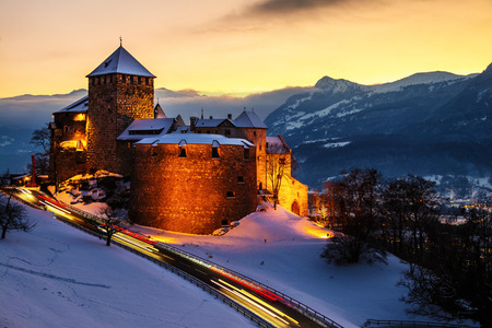 Vaduz, Liechtenstein. Illuminated castle of Vaduz at sunset - popular landmark at night, with car traffic lights and sunset sky, mountains at the background