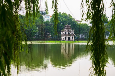 cloudy moody: Hanoi, Vietnam. Turtle Tower at Hoan Kiem Lake in Hanoi, Vietnam. Tree at the foreground, cloudy moody weather