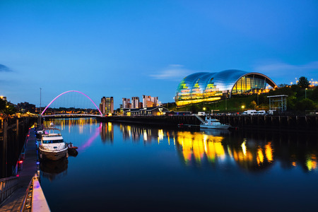 Newcastle upon Tyne, UK. Famous Millennium bridge at night. Illuminated landmarks with river Tyne in Newcastle, UK